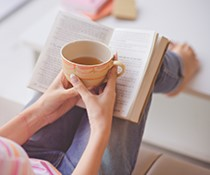 A person reading a book with a cup of tea