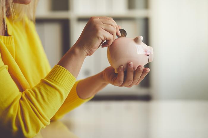 A woman adding coins to a piggy bank